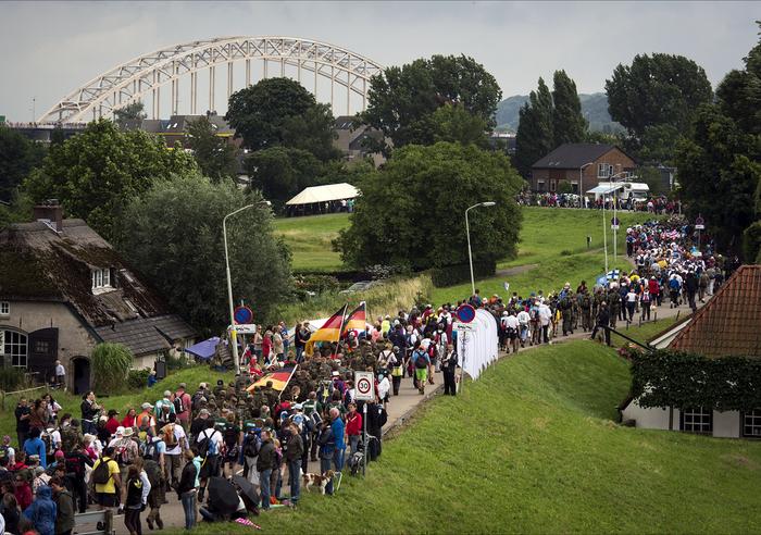 LENT - Deelnemers aan de Vierdaagse wandelen op de Dijk in Lent tijdens de eerste wandeldag van de 96e Nijmeegse Vierdaagse. ANP ERIK VAN 'T WOUD